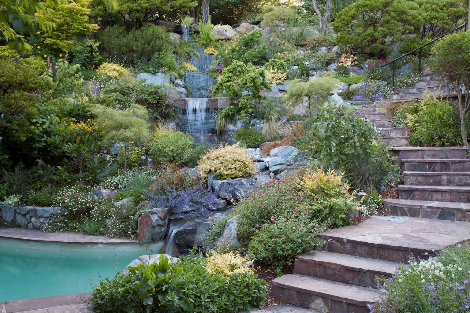 Cut stone path and steps downhillside garden with waterfalls into swimming pool